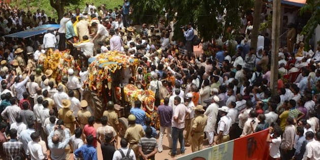 Indian mourners follow the funeral procession for scholar M.M. Kalburgi as he is taken to be buried at Karnataka University in Dharwad on August 31, 2015. Indian scholars on August 31, 2015 condemned the execution-style killing of a leading scholar who had spoken out against idol worship and angered hardline Hindu groups in the run-up to his death. M.M. Kalburgi, an academic and writer from southern Karnataka state, was shot in the forehead after opening the door of his home on August 30 and later died in hospital, police said. AFP PHOTO / STR        (Photo credit should read STRDEL/AFP/Getty Images)