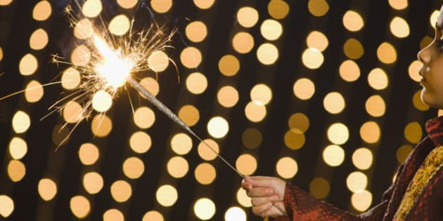 Boy (4-5) holding flashing sparkler during Diwali celebration