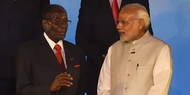 Indian Prime Minister Narendra Modi (R) speaks with Zimbabwe's President Robert Mugabe during the group photograph at the India-Africa Forum Summit in New Delhi on October 29, 2015. Indian Prime Minister Narendra Modi will spell out his vision for the future of his country's economic relations with Africa, as he addresses the major India-Africa Forum Summit in New Delhi.  AFP PHOTO / Money SHARMA        (Photo credit should read MONEY SHARMA/AFP/Getty Images)