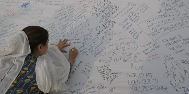 A Pakistani girl writes a message for students killed in a Dec. 16 Taliban attack on a military-run school, in Peshawar, Pakistan, Wednesday, Dec. 24, 2014. The school massacre last Tuesday horrified Pakistanis across the country. The militants, wearing suicide vests, climbed over the fence into a military-run school, burst into an auditorium filled with students and opened fire. The bloodshed went on for several hours until security forces finally were able to kill the attackers. (AP Photo/Muhammad Sajjad)