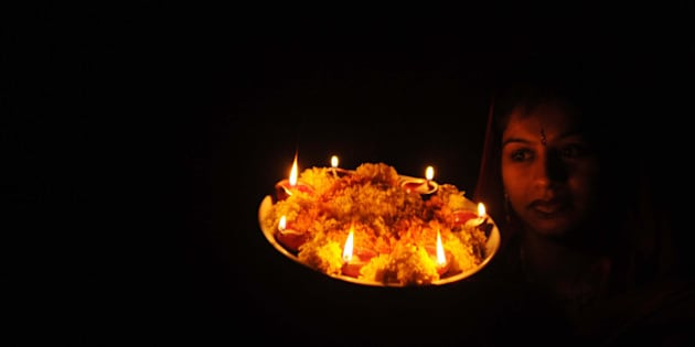 Indian woman Chanda poses with earthenware lamps on the eve of the Hindu festival of Karva Chauth (Husband's Day) in Amritsar on October 14, 2011.  Karva Chauth is a fast undertaken by married Hindu women who offer prayers seeking the welfare, prosperity, well-being, and longevity of their husbands. AFP PHOTO/NARINDER NANU (Photo credit should read NARINDER NANU/AFP/Getty Images)