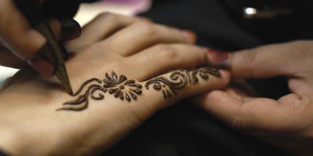 United Arab Emirates, Dubai, applying henna pattern to woman's hand