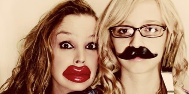 Mother daughter portrait wearing Halloween wax lips and Halloween wax mustache.