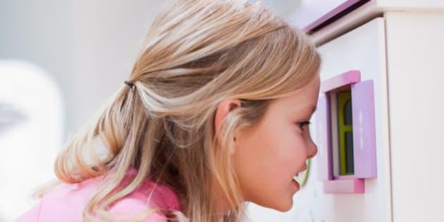 Girl peering into dollhouse