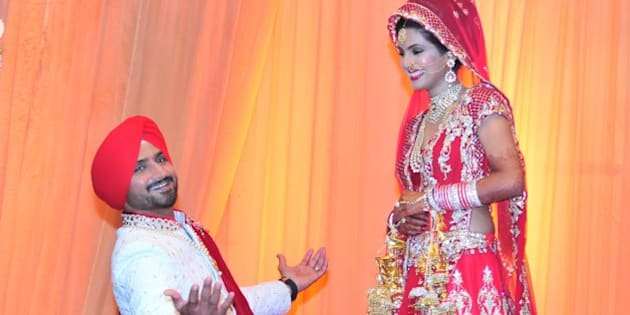 JALANDHAR, INDIA - OCTOBER 29: The newly wedded couple Indian cricketer  Harbhajan Singh got on his knees with wide open arms like Bollywood actor Shah Rukh Khan for actress wife Geeta Basra posing for lensmen after getting married on October 29, 2015 at a resort on the outskirts of Jalandhar, India. Indian ace spinner Harbhajan, 35, and Geeta, who has acted in several Hindi and Punjabi films, have had a five years of courtship before they took the marital plunge. (Photo by Pardeep Pandit/Hindustan Times via Getty Images)