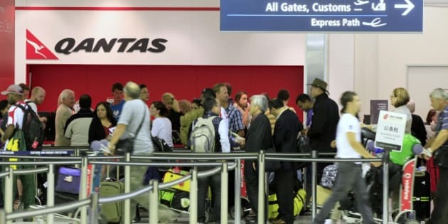 Travelers gather at the Qantas sales desk at Sydney Airport in Sydney, Saturday, Oct. 29, 2011. Qantas Airways grounded its global fleet indefinitely and locked out workers Saturday after weeks of disruptive strikes, and the disappointed Australian government was seeking emergency arbitration. (AP Photo/Rick Rycroft)