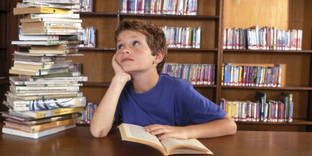 Boy reading by stack of books in library