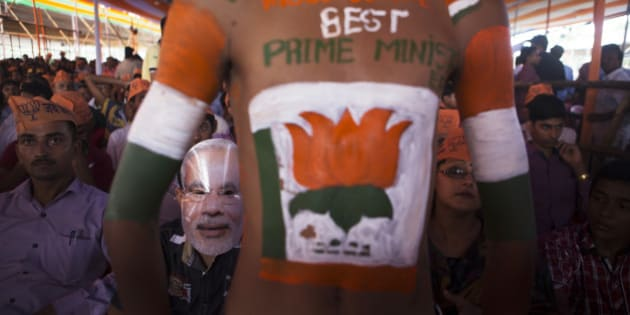 A supporter of the Bharatiya Janata Party (BJP), second left, wears a mask of Indian Prime Minister Narendra Modi during a rally in Muzaffarpur, Bihar, India, on Saturday, July 25, 2015. More than anywhere, Bihar reflects the challenge Prime Minister Narendra Modi faces in overhauling modern India. A vast, landlocked plain bordering the Himalayan nation of Nepal to the north and bisected by the Ganges, India's holiest river, the state is home to about one in 12 Indians. Photographer: Prashanth Vishwanathan/Bloomberg via Getty Images