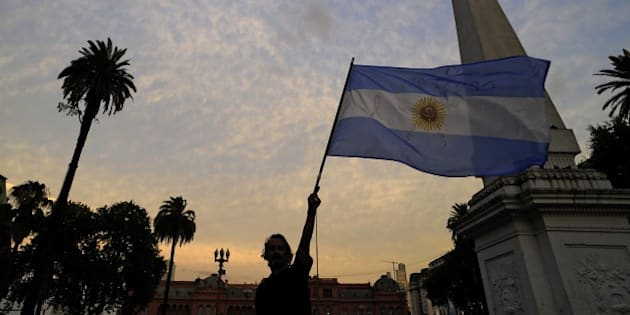 A man holds up an Argentinian flag during a demo at Mayo square, in Buenos Aires on January 19, 2015, against the death of Argentine public prosecutor Alberto Nisman, who was found shot dead earlier, just days after accusing President Cristina Kirchner of obstructing a probe into a 1994 Jewish center bombing. Nisman, 51, who was just hours away from testifying at a congressional hearing, was found dead overnight in his apartment in the trendy Puerto Madero neighbourhood of the capital. 'I can confirm that a 22-caliber handgun was found beside the body,' prosecutor Viviana Fein said. The nation's top security official said Nisman appears to have committed suicide. AFP PHOTO / ALEJANDRO PAGNI   AFP PHOTO / ALEJANDRO PAGNI        (Photo credit should read ALEJANDRO PAGNI/AFP/Getty Images)