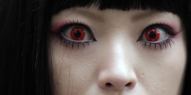 A woman puts on red contact lenses at a Halloween event in Kawasaki, near Tokyo, Sunday, Oct. 28, 2012.(AP Photo/Itsuo Inouye)