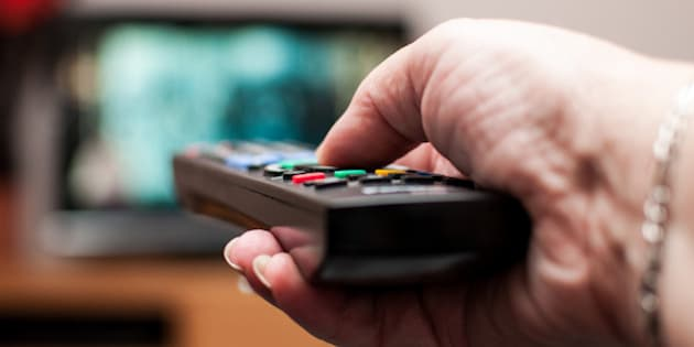 A close up of a woman's hand holding a TV remote control, pointing at the TV in the background.