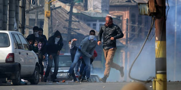 INDIA - 2015/10/30: Kashmiri Muslim protesters throw stones at Indian police during clashes in old Srinagar the summer capital of Indian administered Kashmir. Protesters took to streets in downtown area of Nowhatta shouting slogans in support of Abu Qasim a divisional commander of Lashkar-E-Toiba (a Pakistan based militant outfit) who police claimed had been killed in a gun battle in south Kashmirs Kulgam. Indian Police later fired tear smoke canisters and pellets to disperse any protesters. (Photo by Faisal Khan/Pacific Press/LightRocket via Getty Images)