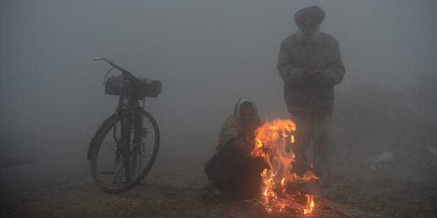 Indian farmers warm themselves around a fire during a dense fog along the India-Pakistan border in Suchit-Garh, 36 kms southwest of Jammu on January 10, 2013.   The beheading of an Indian soldier may have sparked a war of words between Delhi and Islamabad but the two nuclear rivals are both determined to prevent it from wrecking a fragile peace process.  Two Indian soldiers died after a firefight erupted in disputed Kashmir on Tuesday as a patrol moving in fog discovered Pakistani troops about 500 metres (yards) inside Indian territory, according to the Indian army.   AFP PHOTO/Tauseef MUSTAFA        (Photo credit should read TAUSEEF MUSTAFA/AFP/Getty Images)