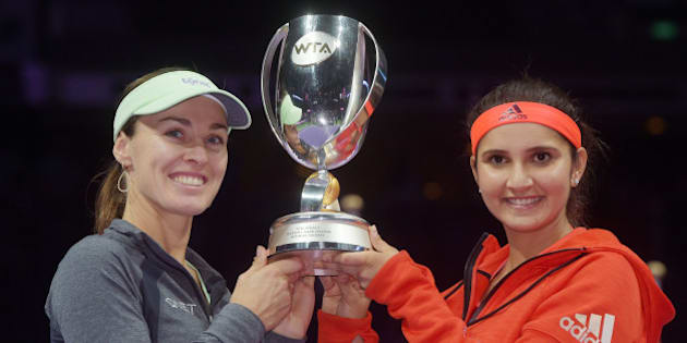 Martina Hingis of Switzerland, left, and Sania Mirza of India, right, pose with their trophy after they beat Carla Suarez Navarro and Garbine Muguruza, both of Spain during the doubles final at the WTA tennis finals in Singapore on Sunday, Nov. 1, 2015.  (AP Photo/Joseph Nair)