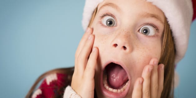 Color image of a little girl with a stressed/shocked/surprised look on her face. She is wearing a Santa hat and an ugly Christmas sweater.
