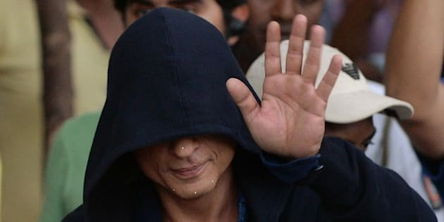 Bollywood actor Shah Rukh Khan, face covered in a hood, waves towards fans as he leaves after finishing the on-location shoot for a film in Mumbai on April 6, 2015.  AFP PHOTO / PUNIT PARANJPE        (Photo credit should read PUNIT PARANJPE/AFP/Getty Images)
