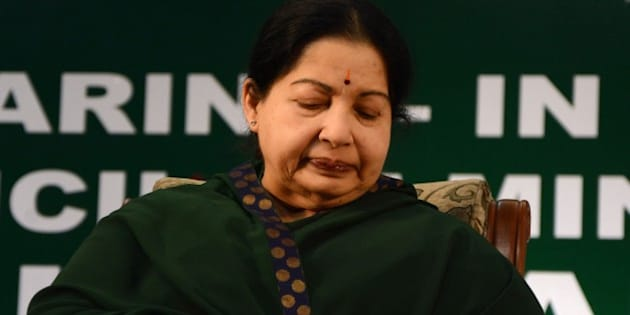 Chief of the All India Anna Dravida Munnetra Kazhagam (AIADMK) party Jayalalithaa Jayaram looks at her watch during her swearing-in ceremony as the chief minister of the southern state of Tamil Nadu in Chennai on May 23, 2015. One of India's most powerful politicians returned May 23, 2015 as chief minister of southern Tamil Nadu state, less than a fortnight after a court acquitted her of corruption. Former film star Jayalalithaa Jayaram was forced to stand down as chief minister of prosperous Tamil Nadu after being found guilty in September 2014 of amassing illegal wealth while in office. AFP PHOTO/STR        (Photo credit should read STRDEL/AFP/Getty Images)