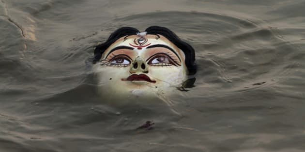 An idol of Hindu goddess Durga floats in water as devotees immerse the same in the River Kuakhai after the Durga Puja festival in Bhubaneswar, India, Sunday, Oct.5, 2014. The immersion of idols marks the end of the festival that commemorates the slaying of a demon king by lion-riding, 10-armed goddess Durga, marking the triumph of good over evil. (AP Photo/Biswaranjan Rout)