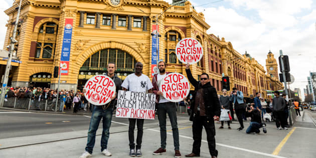 Protestors holding 'Stop racism now' placards stand in front of Flinders Street station during a rally protesting against the forced closure of Aboriginal Communities in Australia