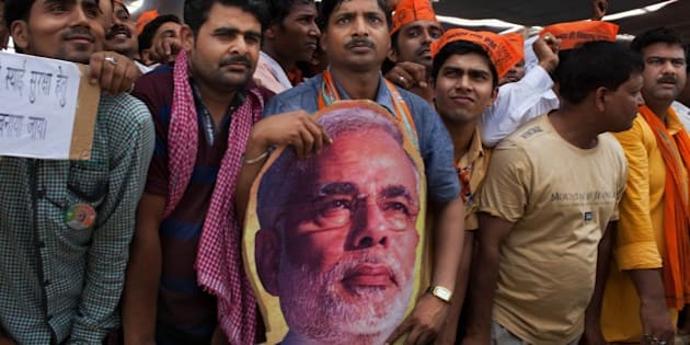 Supporters of India's main opposition and Hindu nationalist Bharatiya Janata Party (BJP) prime ministerial candidate Narendra Modi attend a political rally in Robertsganj, in the northern Indian state of Uttar Pradesh, Saturday, May 10, 2014. During his campaign, Modi has not played up his party's Hindu agenda, but experts say his decision to run from the nearby holy city of Varanasi is meant to send a clear message to all voters about his commitment to the BJP's brand of religious nationalism, which emphasizes India's Hindu identity. (AP Photo/Bernat Armangue)