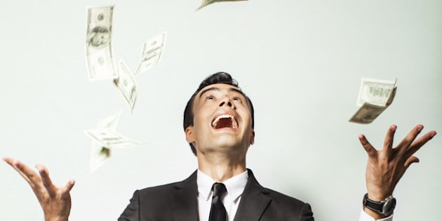 Businessman rejoicing for his success with hundred dollar bills. Money rain concept.