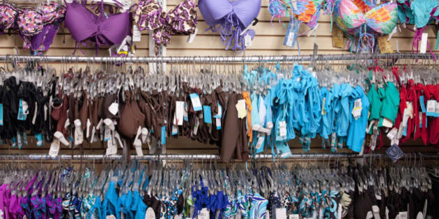 A lot of bathing suits hang on wall at swim wear store