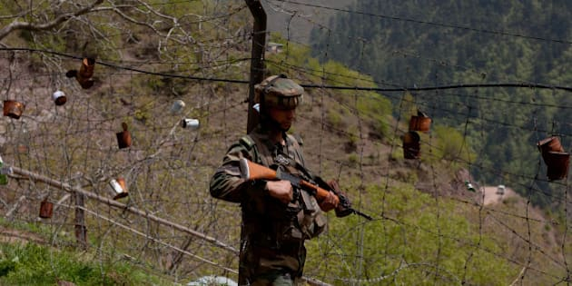 GOHALAN, KASHMIR, INDIA - APRIL 20: An Indian army soldier patrols the fenced area of Line Of Control on April 20, 2015 in Gohalan, 120 Kms (75 miles) north west of Srinagar , the summer capital of Indian administered Kashmir, India. People living along the ceasefire line dividing Kashmir into India and Pakistan-administered portions have continually been at risk due to hostility between the armies of the two nuclear rivals. India on Sunday alledged a ceasefire violation by Pakistan along what New Delhi prefers to call the International Border and Working Boundary by Islamabad, snaking the southern Jammu region of the disputed area. The Indian army in northern Uri district say it has increased its vigil along the Line of Control (LOC), another military line that further divides the region up to the Siachen glaciers. Both Pakistan and India have traded blame over unprovoked shelling which India says is aimed to facilitate the crossover of rebels to their side, a charge Pakistan denies. (Photo by Yawar Nazir/Getty Images)