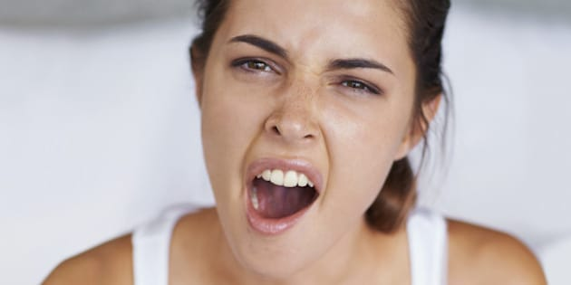 Shot of a young woman giving a big yawn while sitting with a cup of coffee in bed