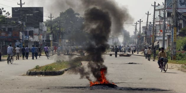Smoke from tires bellows set on fire by the ethnic Madhesis at Birgunj, a town on the border with India, Nepal, Monday, Nov. 2, 2015. Members of the ethnic Madhesi people have been protesting Nepal's new constitution, saying it divides the Madhesis among a number of states. The Madhesis, who want the creation of a larger state that they would dominate, have imposed a general strike in southern Nepal and blocked the border crossing, resulting in a severe fuel shortage across Nepal. (AP Photo/Jiyalal Sah)