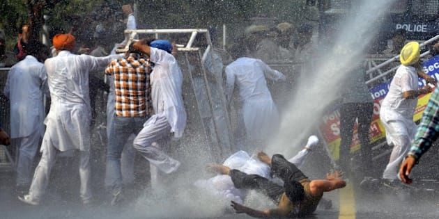 CHANDIGARH, INDIA - OCTOBER 21: Police using the water cannon to spot Simarjit Singh Bains, Independent candidate from Atam Nagar constituency, along with his supporters during the protest against Punjab Chief Minister Parkash Singh Badal outside their residence, on October 21, 2015 in Chandigarh, India. Bains said that the state government is responsible for the incident of sacrilege of Guru Granth Sahib as it fails to arrest the culprits and moreover the two Sikhs were killed in police firing following the orders of the government. (Photo by Gurpreet Singh/Hindustan Times via Getty Images)