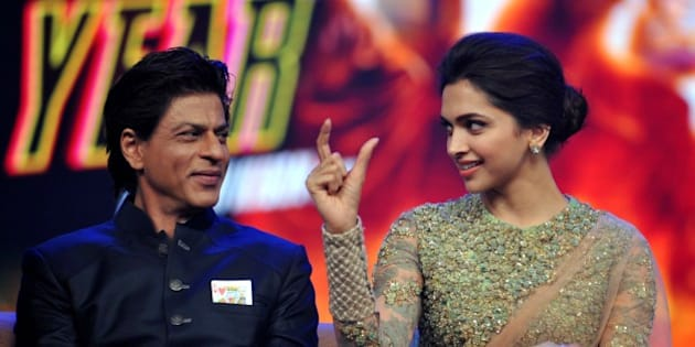 Indian Bollywood actors Shah Rukh Khan (L) and Deepika Padukone talk onstage during a promotional event for the forthcoming Hindi film 'Happy New Year' directed by Farah Khan and produced by Gauri Khan with music directtion by Vishal & Shekhar in Mumbai on late September 15, 2014. AFP PHOTO/STR        (Photo credit should read STRDEL/AFP/Getty Images)