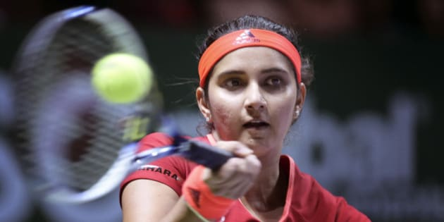 Sania Mirza of India makes a forehand return as she and partner Martina Hingis of Switzerland play Timea Babos of Hungary and Kristina Mladenovic of France during their doubles match at the WTA tennis finals in Singapore on Friday, Oct. 30, 2015.  (AP Photo/Joseph Nair)