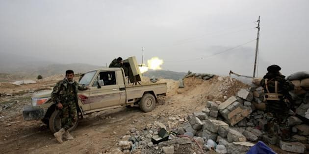 In this Thursday Jan. 29, 2015 photo, a Kurdish peshmerga fighter fires a weapon towards positions of the Islamic State group who are 500 meters or half a mile away, overlooking the strategic town of Sinjar, northern Iraq. (AP Photo/Bram Janssen)