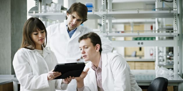 Three scientists in research laboratory discussing project on digital tablet