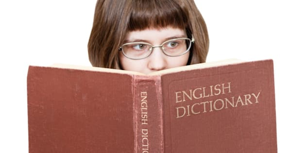 girl with glasses reads big English Dictionary book isolated on white background
