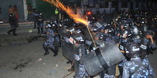 Nepalese roit police fire tear gas at activists from the Brahmin-Chhetri Society outside the Constituent Assembly building, as protesters rally against federalism states in the new constitution, in Kathmandu on May 27, 2012. Nepal's leaders held urgent talks to avoid a political crisis, with just hours remaining before a midnight deadline to agree a new post-war constitution or face the dissolution of parliament.The Constituent Assembly was elected in 2008 after a decade of civil war, with a mandate to write a new national constitution and oversee the peace process that began when the conflict ended in 2006. AFP PHOTO/Prakash MATHEMA        (Photo credit should read PRAKASH MATHEMA/AFP/GettyImages)