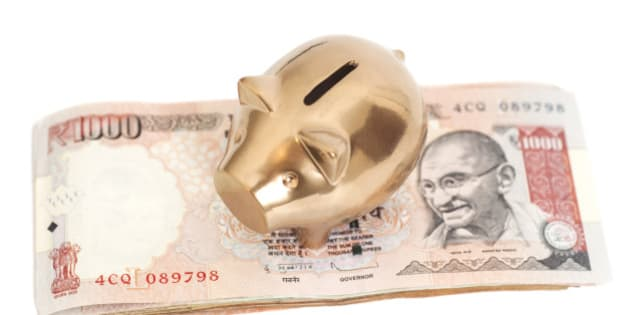 Golden piggy bank on indian 1000 rupee isolated on white