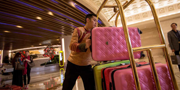 A porter loads a suitcase onto a trolley in the lobby of the Galaxy Macau casino resort, operated by Galaxy Entertainment Group Ltd.,  in Macau, China, on Monday, Mar. 16, 2015. Galaxy, the Macau casino operator that made Lui Che-woo Asia's second-richest person, is scheduled to report earnings on March 19. Photographer: Billy H.C. Kwok/Bloomberg via Getty Images