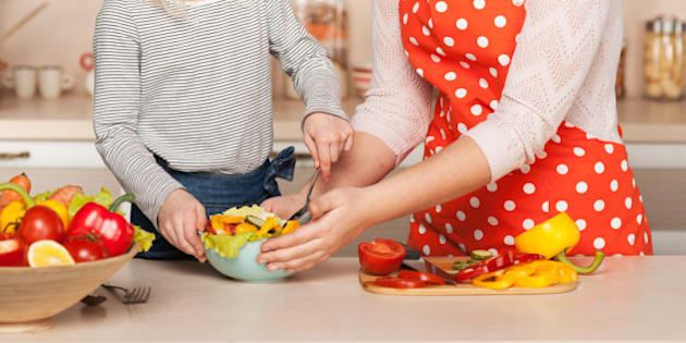 Beautiful smiling young mother and her little daughter cooking salad. Kitchen interior. Concept for young kitchen hands
