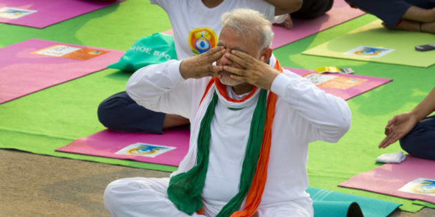 Indian Prime Minister Narendra Modi, performs breathing exercise during yoga along with thousands of Indians on Rajpath, in New Delhi, India, Sunday, June 21, 2015. Millions of yoga enthusiasts are bending their bodies in complex postures across India as they take part in a mass yoga program to mark the first International Yoga Day. (AP Photo/ Manish Swarup)