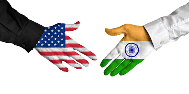 Diplomatic handshake between leaders from the United States and India with flag-painted hands.