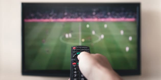 Human hand holding remote control with soccer channel on the television screen.