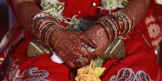 An Indian Muslim bride, her hands decorated with henna, attends a mass wedding organized by a social service organization in Mumbai, India, Sunday, Feb. 15, 2015. Mass weddings in India are organized by social service organizations primarily to help families who cannot afford the high ceremony costs as well as the elaborate dowry that is customary in many communities. (AP Photo/Rafiq Maqbool)