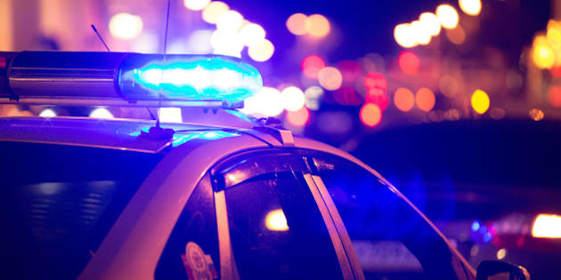 Blue light flasher atop of a police car. City lights on the background.