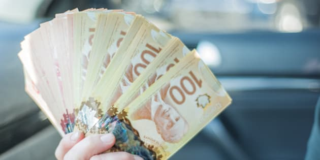 A woman counts $100 Canadian notes/bills before making a large purchase.