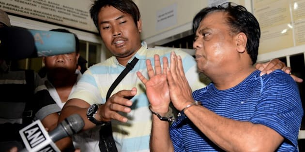 Indian national Rajendra Sadashiv Nikalje, 55, known in India as Chhota Rajan, (R) is held by Indonesian police prior to being escorted from Bali police headquarters to Ngurah Rai Airport during his deportation to India from Denpasar on Bali island on November 5, 2015. The Indian fugitive wanted over a series of murders in his country has been arrested in Indonesia after decades on the run, police said.  vAFP PHOTO / SONNY TUMBELAKA        (Photo credit should read SONNY TUMBELAKA/AFP/Getty Images)