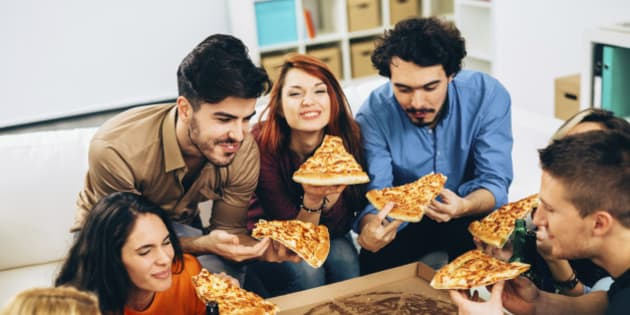 Group of friends eating pizza together.