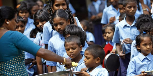 A teacher distributes free mid-day meal to Indian schoolchildren at a government run school on World Food Day in Bangalore, India, Tuesday, Oct. 16, 2012. Blaming flawed methodology and poor data, the United Nations says its 2009 headline-grabbing announcement that 1 billion people in the world were hungry was off-target and that the number is actually more like 870 million. (AP Photo/Aijaz Rahi)