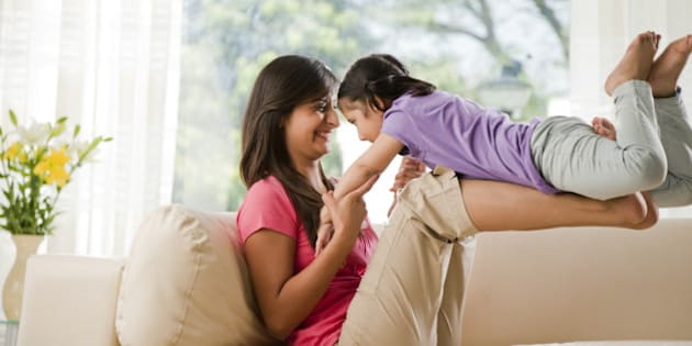 Mother playing with daughter (6-7) on sofa