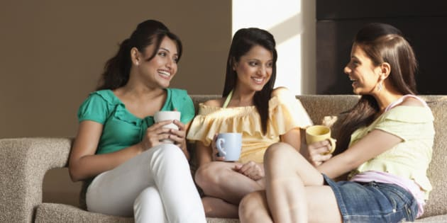 Three young students drinking coffee in living room